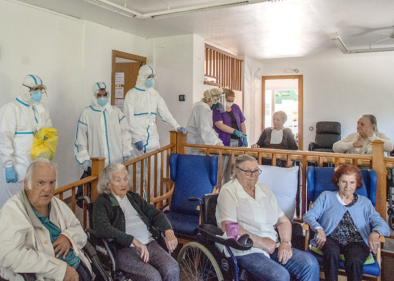 Health care nurses in PPE with the elderly residents at a retirement home in Spain.