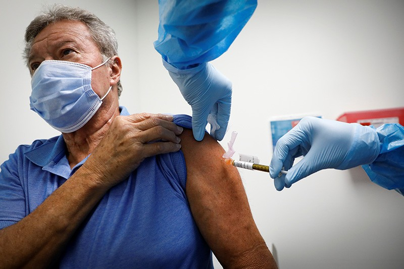 A volunteer is injected with a COVID-19 vaccine for a study in the United States.
