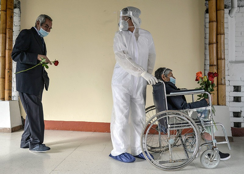 An elderly man holding a flower follows a worker pushing his wife in a wheelchair as she leaves intensive care.