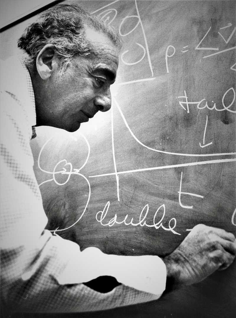 Historical portrait of Berni Alder writing on a blackboard