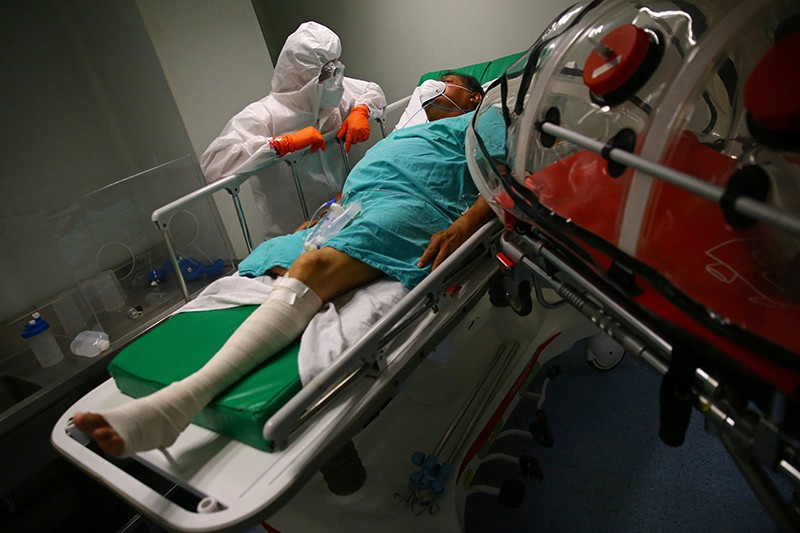 A patient suffering from the COVID-19 rests on his bed as paramedics transfer him between hospitals in Mexico City