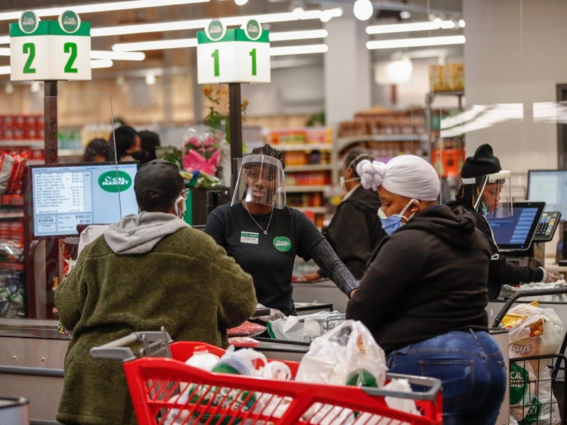 A cashier wearing a face shield talks with a customer at the Local Market Foods store in Chicago, April 2020.