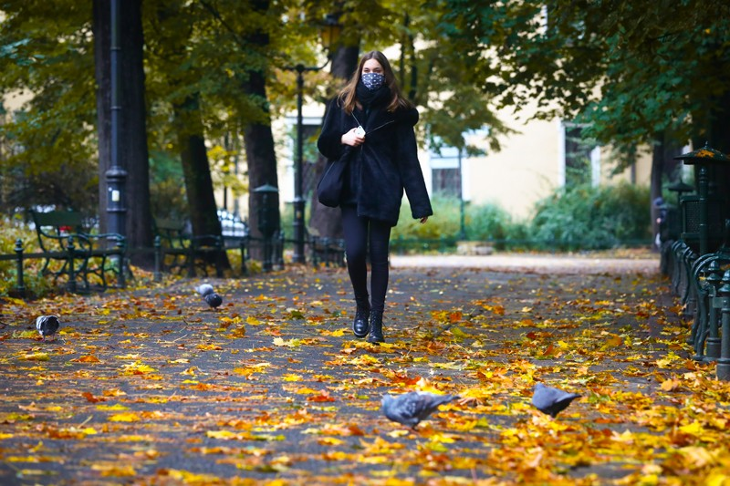 A young woman wears a face mask while walking through a park with autumn leaves.
