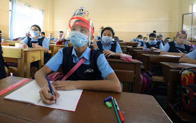 Pupils sitting at desks wearing face masks.