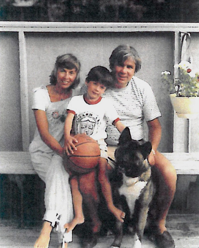Joey, Joe and Kathy O'Donnell sit on a bench with their dog at their feet.