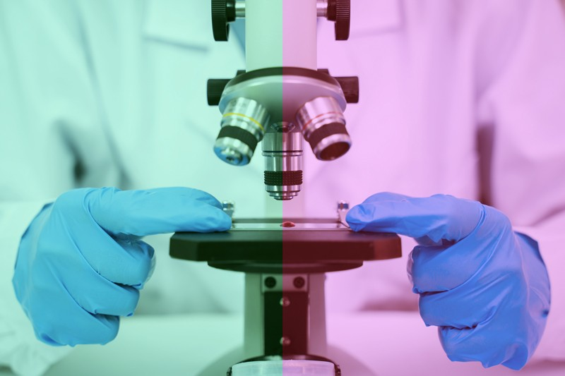 Researcher in a lab coat and gloves uses a microscope. The picture has a green tint on the left and a red tint on the right.