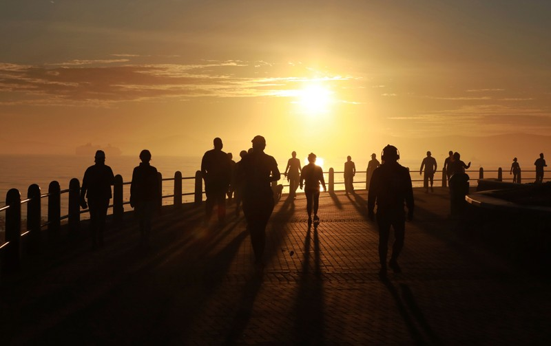 People exercise along the promenade at sunrise in Sea Point, Cape Town
