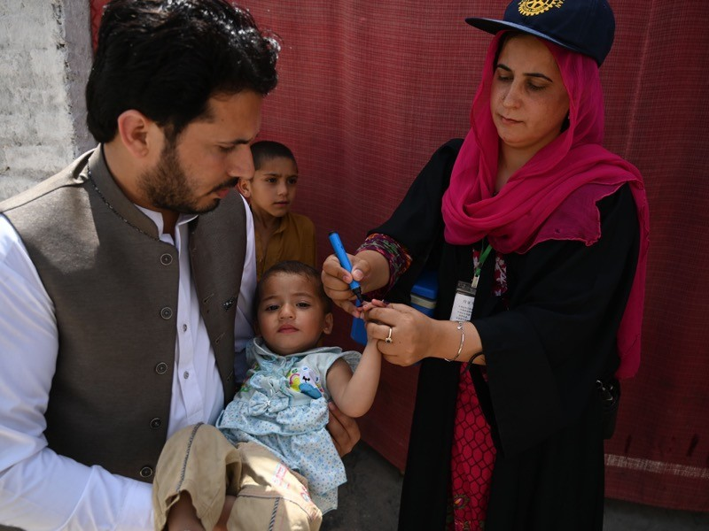 A health worker marks a child's finger after administering anti-polio drops.