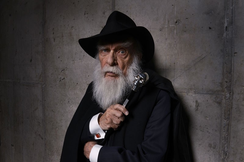 James Randi poses for a portrait against a concrete wall wearing a black brimmed hat and holding a cane with a skull topper