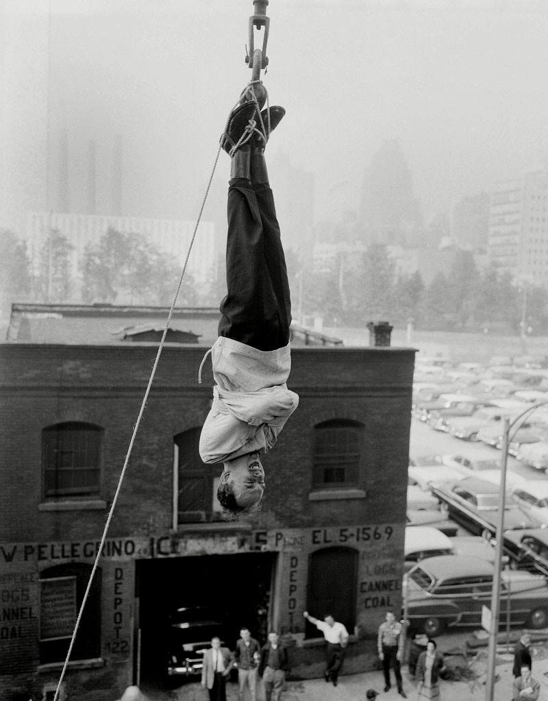 James Randi performing an escape stunt in a strait jacket while suspended from a crane above New York in 1956
