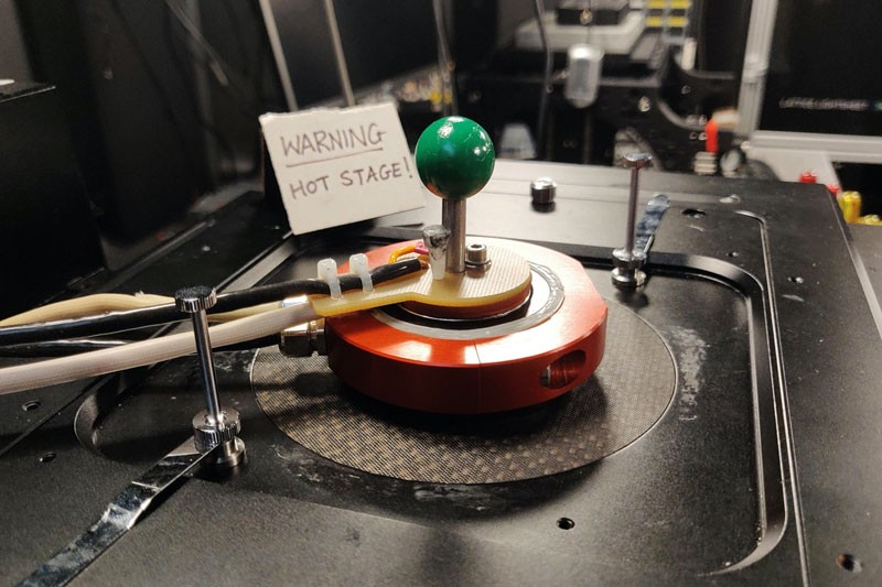 "Lab apparatus made up of a red disc and a green spherical handle with a sign in the background reading ""Warning, hot stage"""