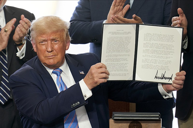 U.S. President Donald Trump holds up a signed executive order
