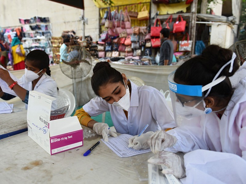 Health workers wait to collect swab samples from residents to test for the Covid-19, India.