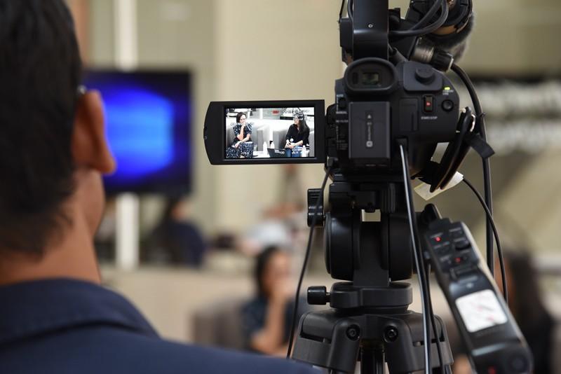 A cameraman recording two women talking.