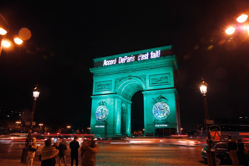 "The Arc de Triomphe is illuminated in green with the words ""Paris Agreement is Done"""