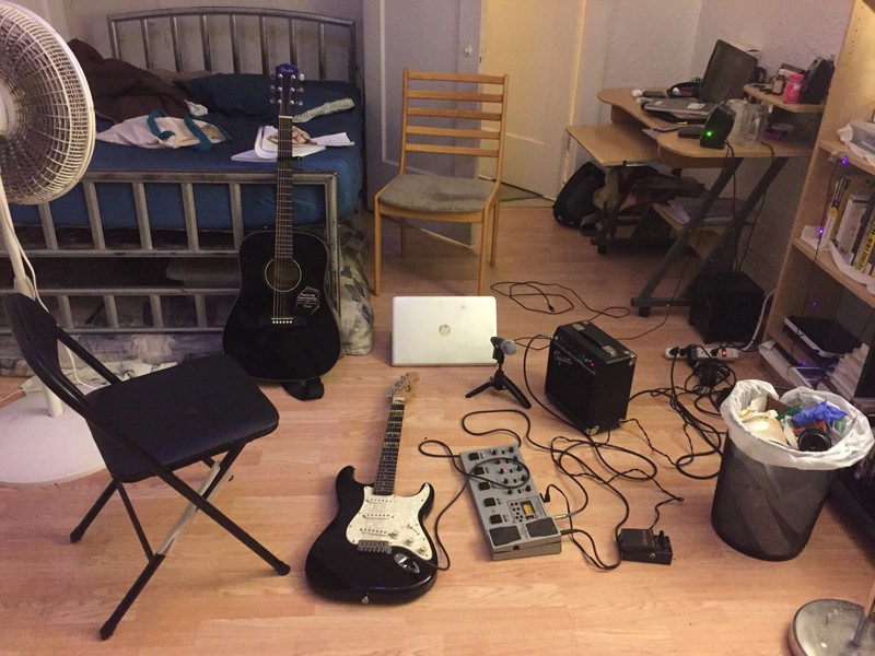 Two guitars and other musical equipment in a bedroom.