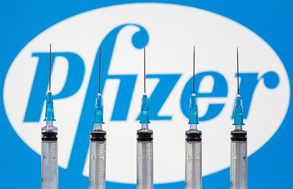 Syringes are seen in front of displayed Biontech and Pfizer logos