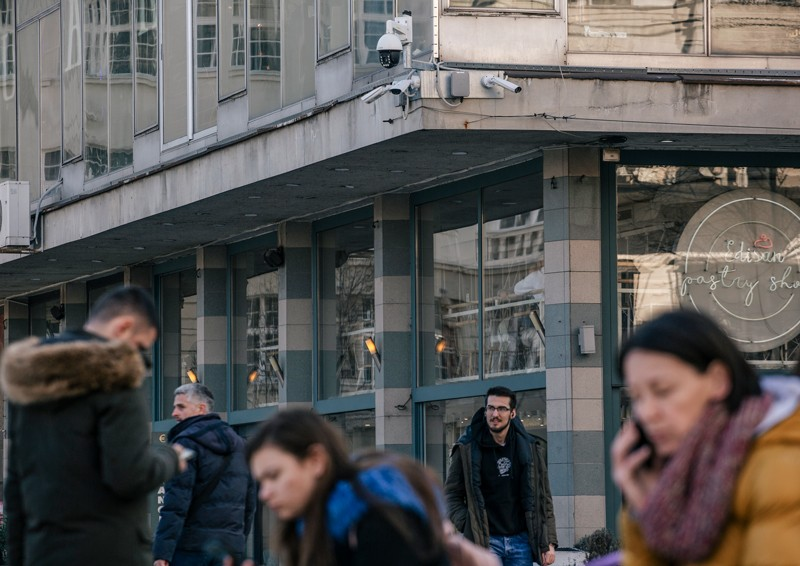 Surveillance cameras installed on the corner of a building overlooking people in the public square below