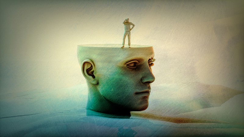 A small human figure stands on a stylized human head with a flattened top like a table