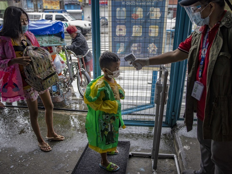 A boy has his temperature checked as a measure against COVID-19, as they arrive at an evacuation center, Manila.
