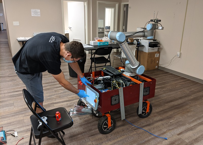 Dean Conte working on a robot in a health centre