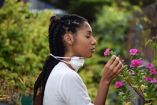A young woman takes face mask off to smell the flowers