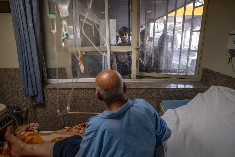 An elderly male patient in a hospital bed talks to relatives through a window in a hospital in Iran
