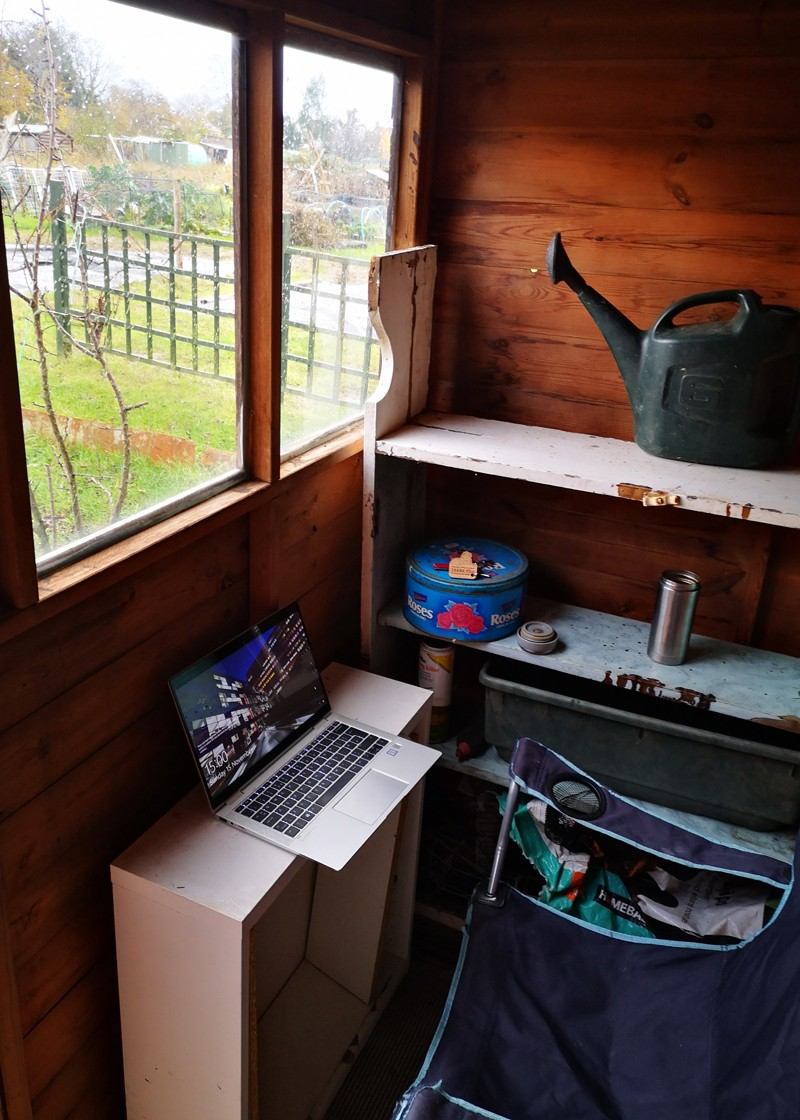 A view of a laptop and chair inside John's shed