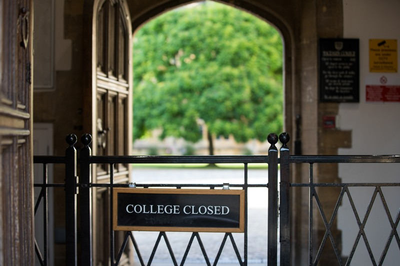 A gate displaying a closed sign stands at the entrance to Magdalen College