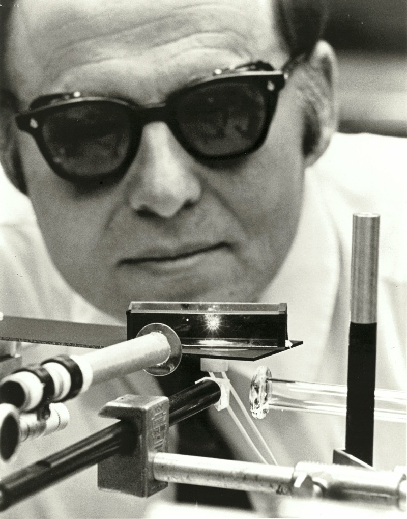 Black and white photo of Arthur Ashkin wearing dark goggles looking at laser equipment in the lab in 1971