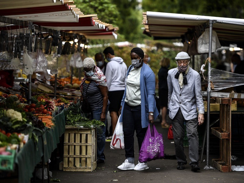 People wearing protective face masks shop at a n open air market in Paris on August 28, 2020.