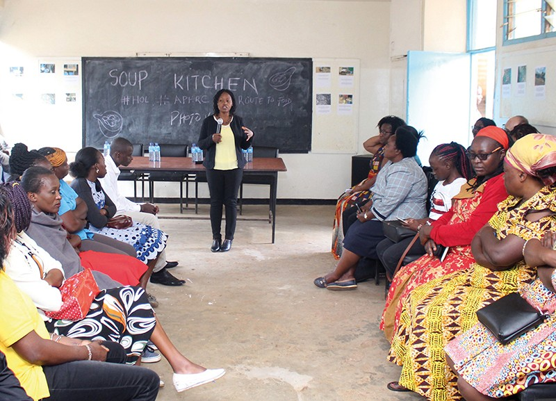Elizabeth Kimani-Murage stands talking to a group of seated women