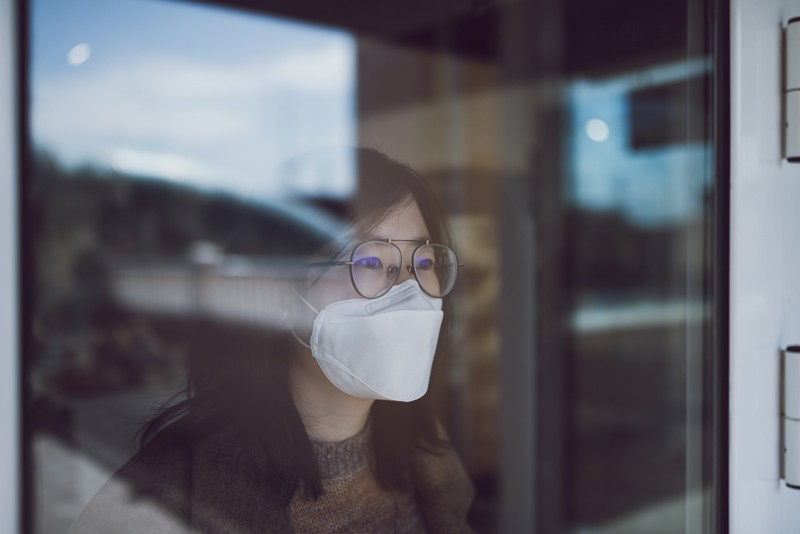 Woman looking through a window wearing a mask