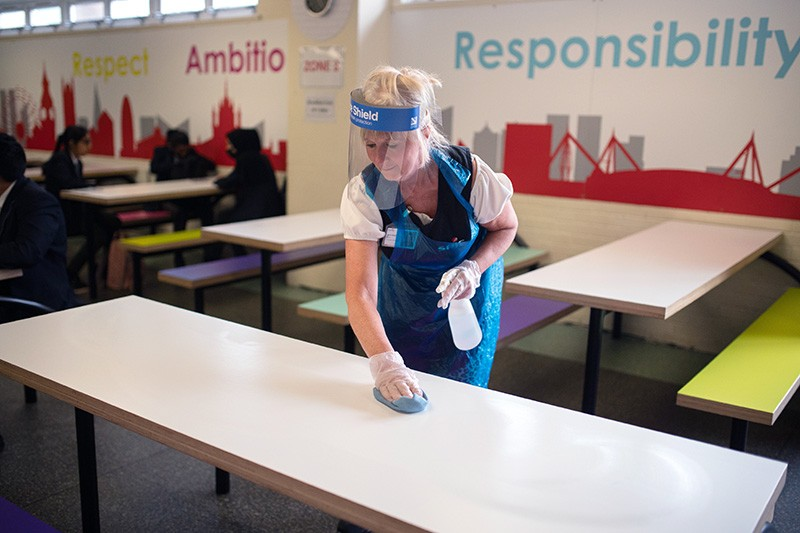 A cleaning staff member wearing PPE sanitises tables and chairs in a school