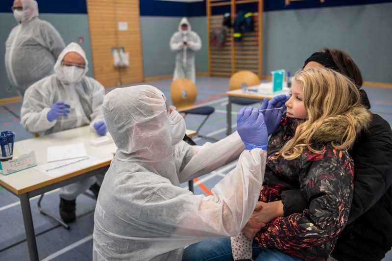 A health-care worker takes a nasal swab from a girl being held in her mother's arms.