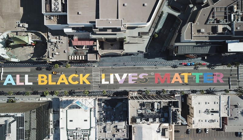 "Overhead view of the words ""All Black Lives Matter"" painted on a road"