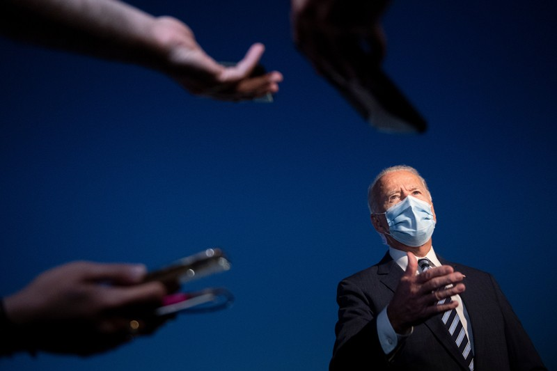 Joe Biden wearing a face mask talks to reporters pointing microphones at him