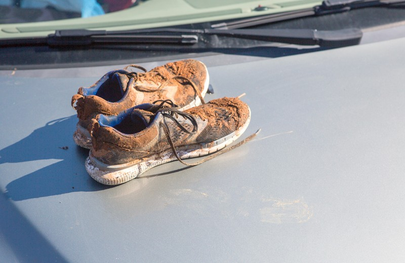 Muddy running shoes on the bonnet of a silver car