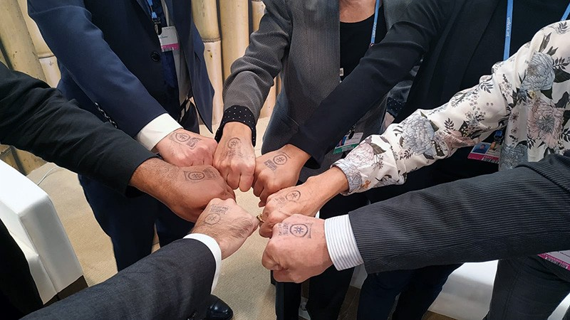 People show their hand stamps in a circle at the VirtualBlueCOP25