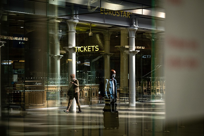 People with luggage and wearing masks walk to the Eurostar train in St Pancras International Station, London