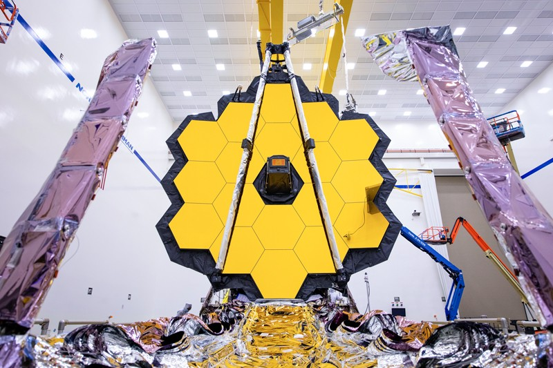 A large yellow mirror made up of many hexagons in a honey comb pattern makes up part of the James Webb telescope