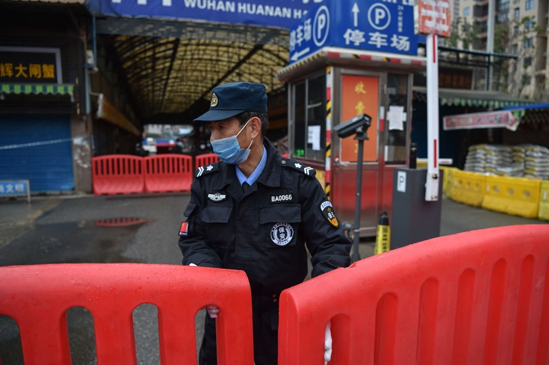 A policeman wearing a face mask stands behind red barriers at the entrance of a large covered market