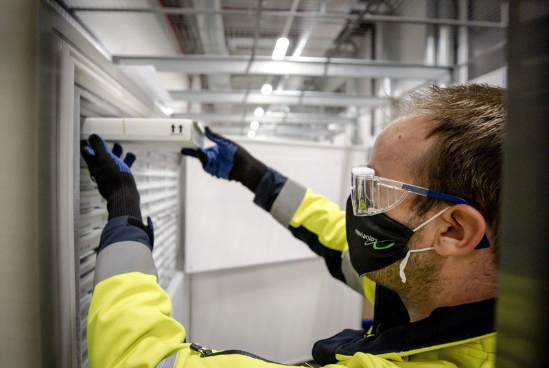 A medical worker wearing a facemask, protective goggles and gloves stores a container of vaccines into a refrigeration unit