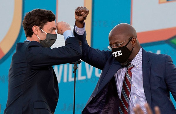 Democratic candidates for Senate Jon Ossoff and Raphael Warnock bump elbows.