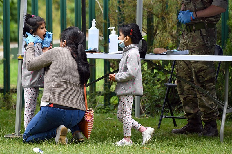 A family member administers a COVID-19 self-test on a child at an outdoor park in London