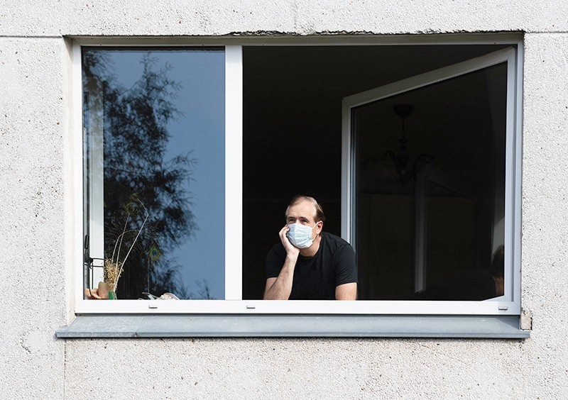 Man wearing a face mask looking out of a window