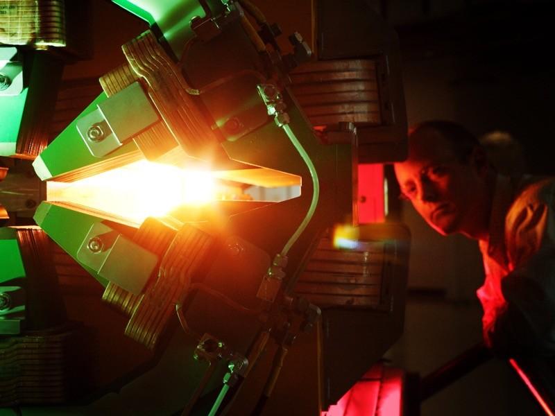 Ein Mann schaut auf einen Magnetapparat in einem Synchrotron.