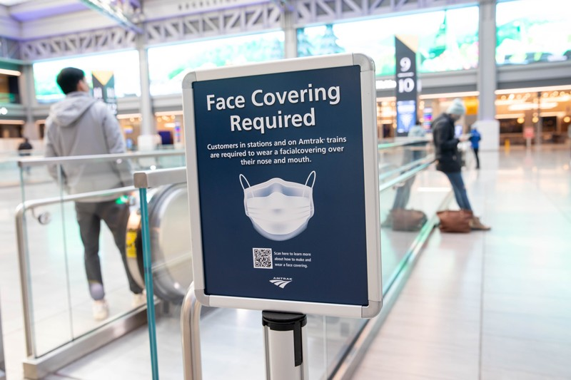 A sign advertising a face mask requirement is displayed at the Moynihan Train Hall in New York