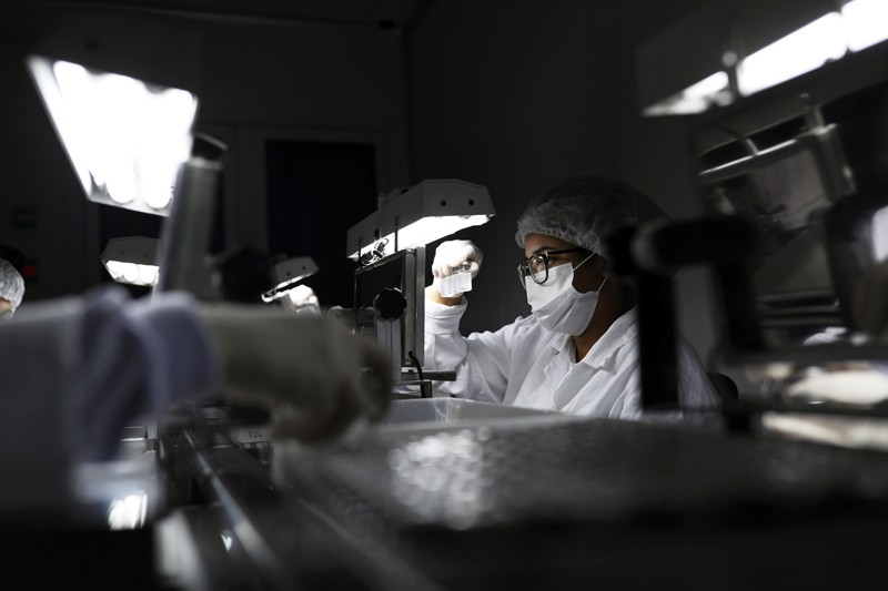 An employee wearing a protective mask and hair net inspects vials containing a COVID-19 vaccine under a light