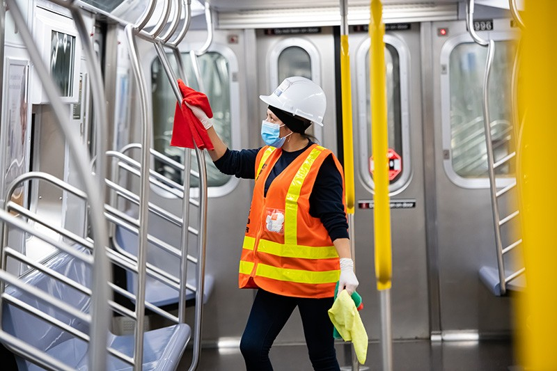 An MTA cleaning contractor cleans and disinfects a New York City subway car